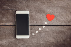 Smartphone and hearts paper on wooden background Stock Photos