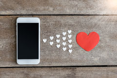 Smartphone and hearts paper on wooden background Royalty Free Stock Image