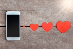 Smartphone and hearts paper on wooden background Royalty Free Stock Photography