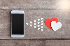 Smartphone and hearts paper on wooden background Stock Photography