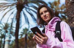 Η λαβή κοριτσιών στο κινητό τηλέφωνο χεριών, μήνυμα τύπων προσώπων στο smartphone, χαλαρώνει τα ταξίδια τουριστών προγραμματίζοντ στοκ εικόνες με δικαίωμα ελεύθερης χρήσης