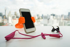 Smartphone with holder stand with pink wireless earphone Royalty Free Stock Photos