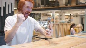 Smartphone, homme roux de barbe célébrant le succès du travail photo stock