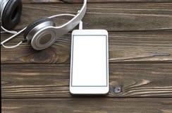 Smartphone, hoofdtelefoons op de achtergrond van een houten lijst Royalty-vrije Stock Foto's
