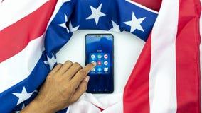 Smartphone Huawei Y9 2019 för asiatiskt handlag för man för Phuket Thailand May-24-2019 handaffär mobil med amerikanska flaggan,  royaltyfria bilder