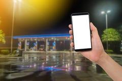Smartphone humano da posse da mão, tabuleta, telefone celular com a tela vazia no fundo obscuro do posto de gasolina Imagens de Stock Royalty Free