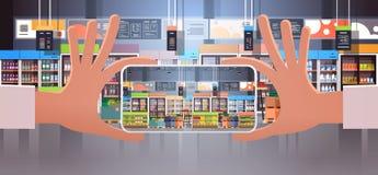 Smartphone humano de la tenencia de la mano que toma a foto el interior moderno del supermercado con el surtido de la comida del  libre illustration