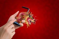 Smartphone humano del control de la mano, tableta, teléfono celular con el dragón grande s Fotos de archivo libres de regalías