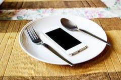 Smartphone i den vita maträtten Arkivfoto