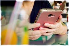 Smartphone i en ros och en guld kulöra Flip Case royaltyfria bilder