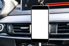 Smartphone i ett bilbruk för Navigate eller GPS Körning av en bil med Smartphone i hållare Mobiltelefon med den isolerade vita sk Arkivbilder