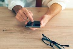 Smartphone i händer av den lyckade affärsmannen Arkivbilder