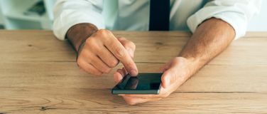 Smartphone i händer av den lyckade affärsmannen Royaltyfria Bilder