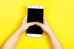 Smartphone i händerna av ett barn Arkivfoton