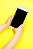 Smartphone i händerna av ett barn Arkivfoto
