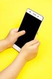 Smartphone i händerna av ett barn Fotografering för Bildbyråer