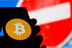 Smartphone i hand med Bitcoin cryptocurrencylogo Förbjuda det röda tecknet på bakgrund arkivfoton