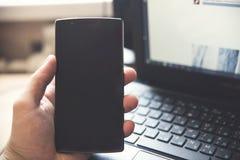 Smartphone i handen, bärbar dator royaltyfri foto