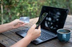Smartphone i karty kredytowe w ręce z laptopem i kawą na drewnianym stole obraz stock