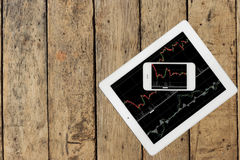 Smartphone i pastylka z wykresem na drewno stole Zdjęcie Stock