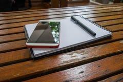 Smartphone i pióro stawiający dalej pusty notatnik na drewnie Zdjęcie Royalty Free