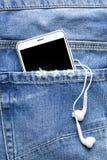 Smartphone i słuchawki w kieszeni cajgi zdjęcia royalty free