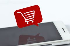 Smartphone i wiadomość gulgoczemy z wózkiem na zakupy - Online zakupy pojęcie obraz royalty free