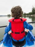 Smartphone image young boy in red life jacket kayaking from behi Stock Photo