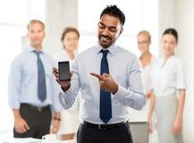 Smartphone indien d'apparence d'homme d'affaires au bureau photographie stock