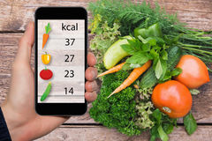Smartphone with information on the amount of calories in vegetables. Stock Photos