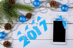 Smartphone 2017 and the inscription on the wooden table, top vie. W. New year decoration on a wooden table Royalty Free Stock Photo