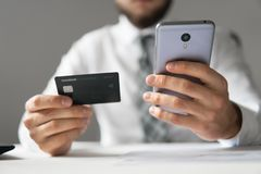 Smartphone and Internet Commerce. Payment of goods online. Young businessman with a bank credit card stock photos