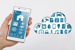 Smartphone internet of things cloud. Smartphone used for controlling devices in smart home interconnected over the Internet of Things, illustrated by a cloud Royalty Free Stock Image