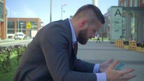 Smartphone irritado da consultação do homem de negócios, steadicam video estoque