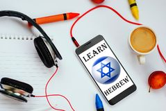 Learn Hebrew concept. Smartphone with Israel flag and headphones. concept of hebrew learning through audio courses stock photography
