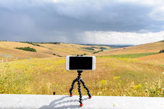 A smartphone on its magnetic tripod. Ready to shoot a video or a photo stock image
