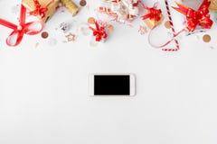 Smartphone julsammansättning Julgåvor och garneringar på vit bakgrund Lekmanna- bästa sikt för lägenhet Arkivbilder