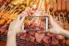 Smartphone kamera som tar ett foto av skinka- och korvpinnar på gatamarknaden royaltyfria foton