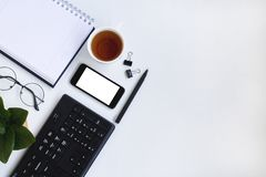 Smartphone, keyboard, notebook and cup of tea on white office desk. royalty free stock photos