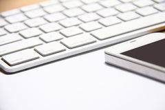 Smartphone and keyboard on table. Royalty Free Stock Image
