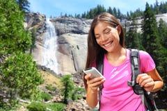 Smartphone - kvinnafotvandrare som använder den smarta telefonen på vandring Royaltyfri Foto