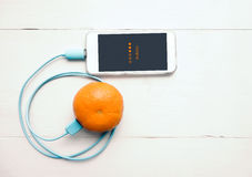 Smartphone laddande batteri från orange frukt, Smart och Eco - F Arkivbild