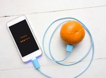 Smartphone laddande batteri från orange frukt, Smart och Eco - F Royaltyfria Foton