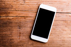 Smartphone laid on an old office desk, copy space Royalty Free Stock Images