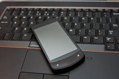 Smartphone on laptop computer Royalty Free Stock Images