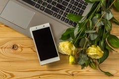 Smartphone, laptopu i eustoma kwiaty na drewnianym backgr, Zdjęcia Stock