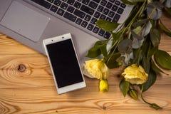 Smartphone, laptopu i eustoma kwiaty na drewnianym backgr, Fotografia Royalty Free
