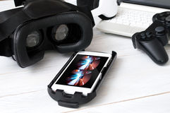 Smartphone laying on desk and prepared to play with VR googles. Game on screen was created in graphic program Stock Image