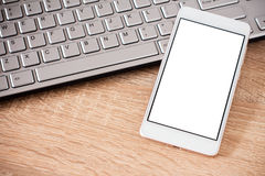 Smartphone laying on laptop keyboard Stock Images