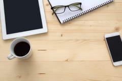 Smartphone, libreta, vidrios y cuaderno con una taza de café en la tabla Imagen de archivo